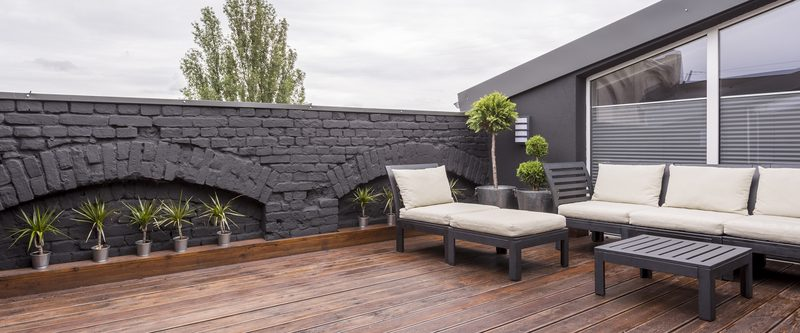Panorama view of modern rooftop terrace with dark wood deck flooring, plants, brick fence and black garden furniture P